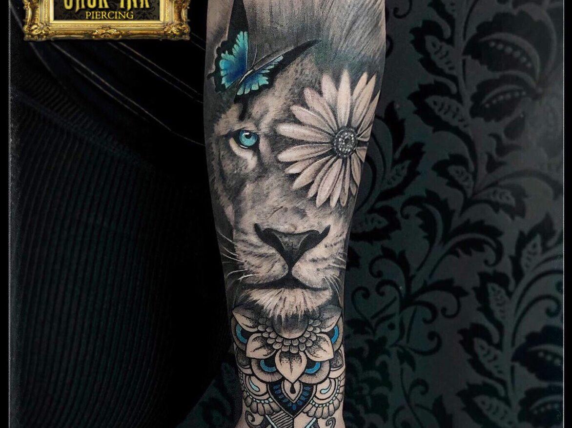 Tatuaj cap de leu cu floare si fluture color pe antebrat